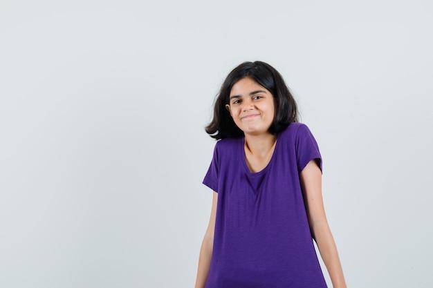 Mała dziewczynka w koszulce wzrusza ramionami i wygląda wesoło,