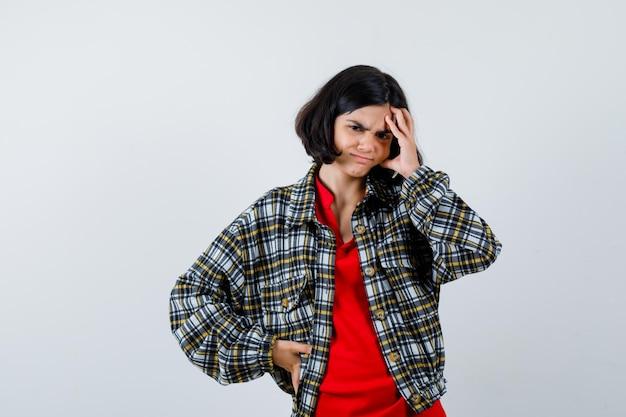 Mała dziewczynka w koszuli, kurtce, cierpi na ból głowy i wygląda na bolesny, widok z przodu.