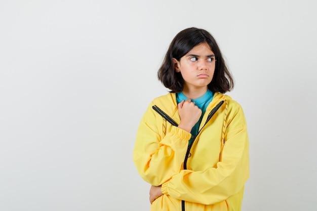 Mała dziewczynka w koszuli, kurtce, odwracając wzrok, trzymając rękę na klatce piersiowej i patrząc zamyślony, widok z przodu.