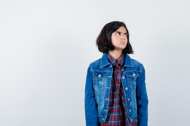 Mała dziewczynka w koszuli, kurtce, patrząc na bok i patrząc zamyślony, widok z przodu.