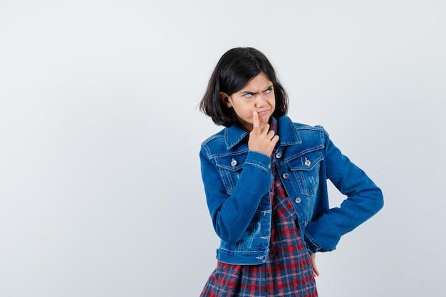 Mała dziewczynka w koszuli, kurtce, trzymając palec w pobliżu ust i patrząc zamyślony, widok z przodu.