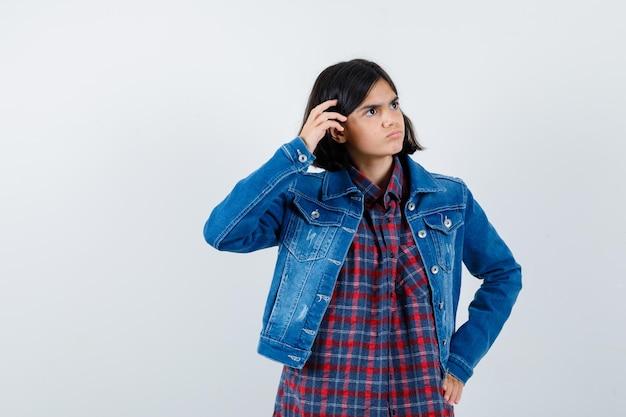 Mała dziewczynka w koszuli, kurtce, trzymając rękę na głowie i patrząc zamyślony, widok z przodu.