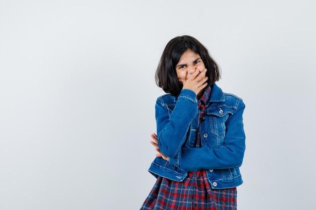 Mała dziewczynka w koszuli, kurtce, trzymając rękę na ustach i patrząc szczęśliwy, widok z przodu.