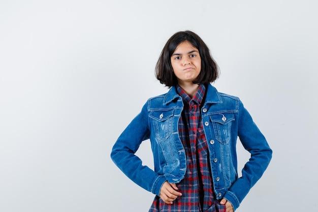 Mała dziewczynka w koszuli, kurtce, trzymając się za ręce w talii i patrząc ponury, widok z przodu.