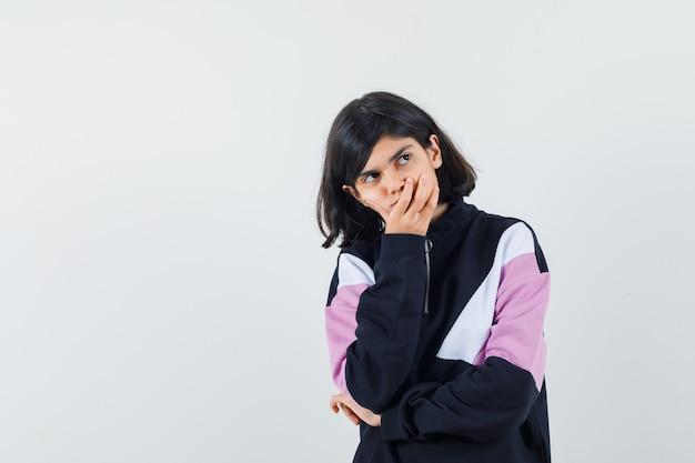Mała dziewczynka w koszuli, trzymając dłoń na ustach i patrząc zamyślony, widok z przodu.