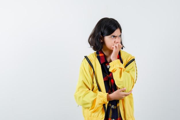 Mała dziewczynka w kraciastej koszuli, kurtce, trzymając rękę na ustach i patrząc poważnie