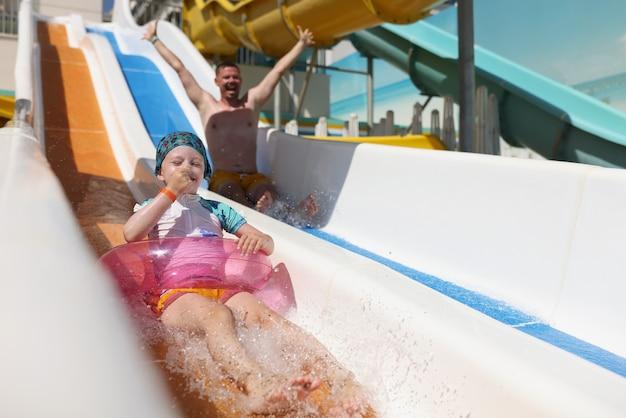Mała dziewczynka w kręgu pływackim i ojciec jeżdżący kolejką górską w parku wodnym