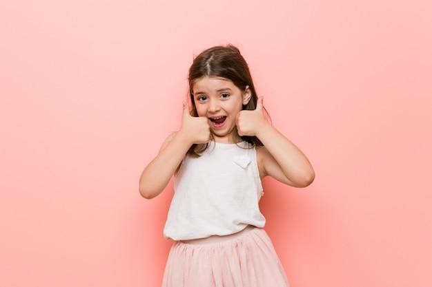 Mała dziewczynka w księżniczce wygląda na unoszącą kciuki do góry, uśmiechnięta i pewna siebie.