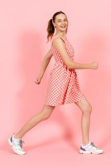 Mała dziewczynka w ładny jasny strój pozuje szczęśliwie na różowo