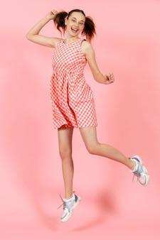 Mała dziewczynka w ładny jasny strój skoki na różowo
