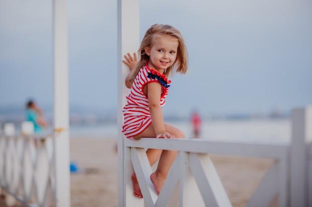 Mała dziewczynka w lato sukni obsiadaniu na białym ogrodzeniu na piaska dennym wybrzeżu.