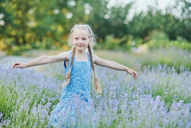 Mała dziewczynka w lawendy polu. fantazja dla dzieci. uśmiechnięty dziewczyny obwąchanie kwitnie w lato lawendy purpurowym polu.