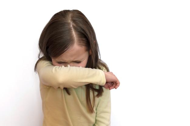 Mała dziewczynka w lekkim swetrze na białym szarym tle kicha w łokieć