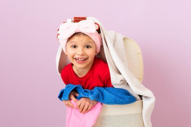 Mała dziewczynka w lokówkach będzie myła brudne rzeczy. pranie i czyszczenie chemiczne.