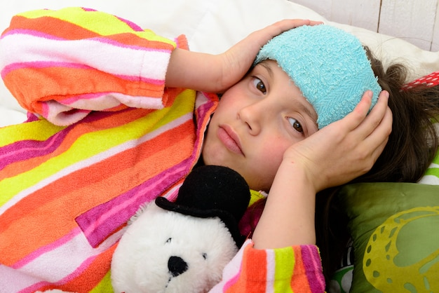 Mała dziewczynka w łóżku ma ból głowy