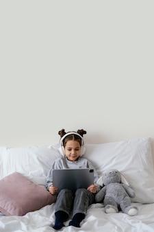 Mała dziewczynka w łóżku ze słuchawkami za pomocą tabletu