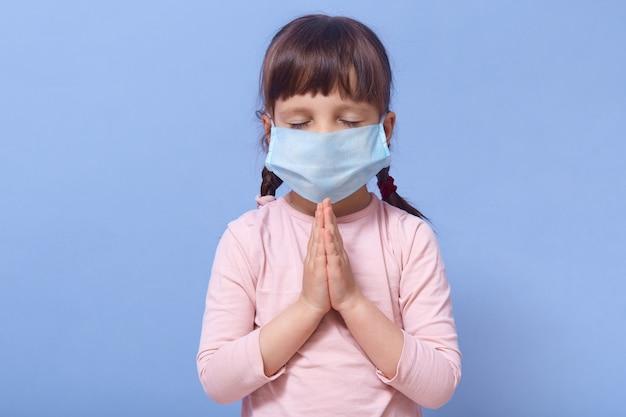 Mała dziewczynka w masce dla ochrony fron covid 19, stojąc z zamkniętymi oczami