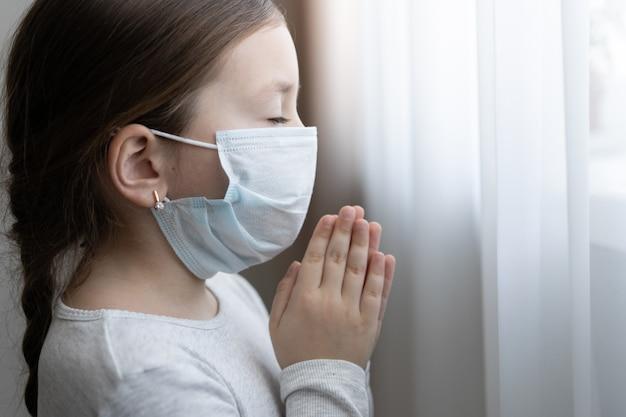 Mała dziewczynka w masce do ochrony covid-19. modliła się rano o nowy dzień wolności dla światowego wirusa koronowego. mała dziewczynka ręka modląc się o dziękuję bogu