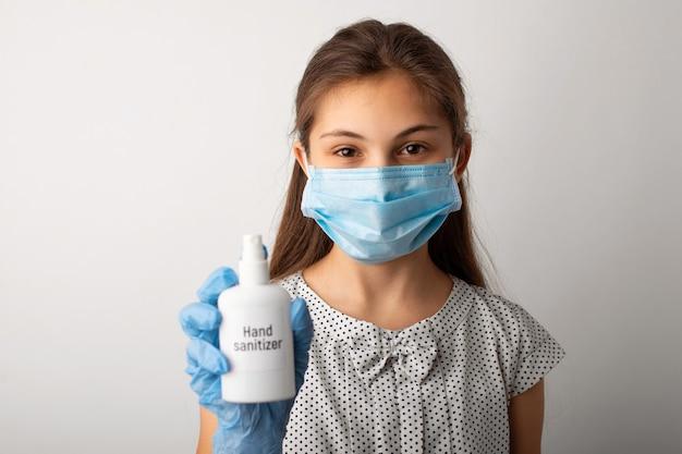 Mała dziewczynka w masce medycznej i rękawiczkach pokazuje środek dezynfekujący do rąk