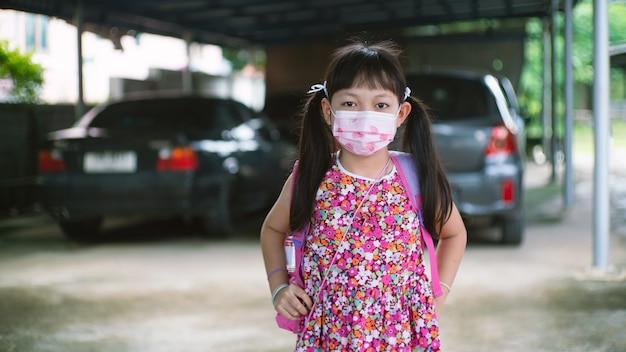 Mała dziewczynka w masce na twarz wraca do szkoły po kwarantannie i zamknięciu covid-19