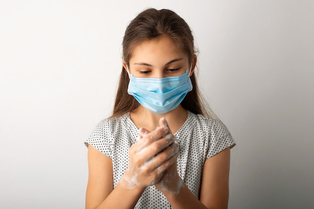 Mała dziewczynka w masce ochronnej dróg oddechowych dokładnie myje ręce