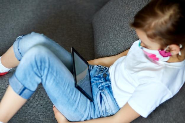Mała dziewczynka w masce ochronnej za pomocą, grać na tablecie lub uczyć się podczas rozmowy wideo online