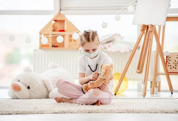 Mała dziewczynka w maskowej bawić się lekarce