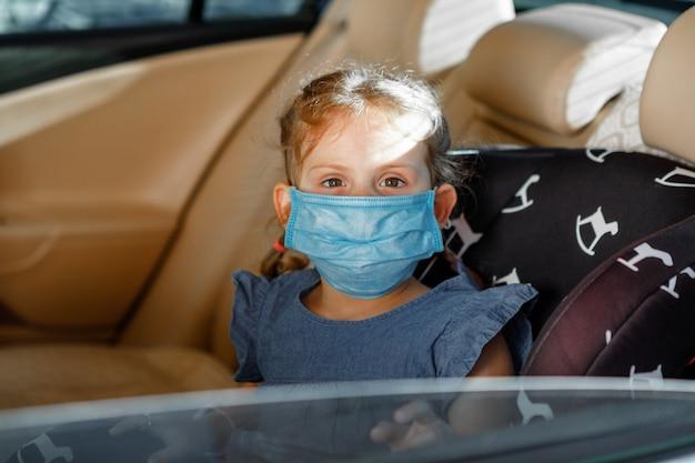 Mała dziewczynka w medycznej masce siedzi w dziecięcym siedzeniu w samochodzie.