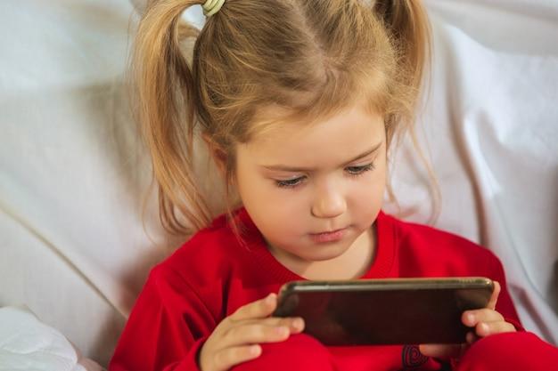 Mała dziewczynka w miękkiej ciepłej piżamie bawi się w domu