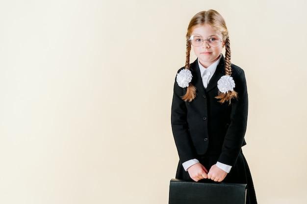Mała dziewczynka w mundurku szkolnym z warkoczykami trzyma teczkę
