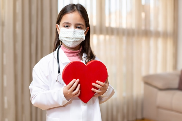 Mała dziewczynka w mundurze lekarza i masce medycznej, trzymając w dłoniach wielkie serce