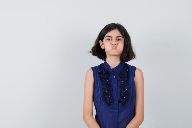 Mała dziewczynka w niebieskiej bluzce dmuchanie w policzki i ładny wygląd, widok z przodu.