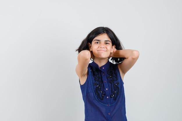 Mała dziewczynka w niebieskiej bluzce trzymając się za ręce za głową i patrząc wesoło, widok z przodu.