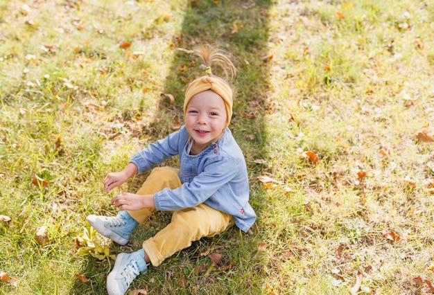 Mała dziewczynka w niebieskiej koszuli i żółtych spodniach siedzi na trawie w parku i uśmiecha się, patrząc w górę