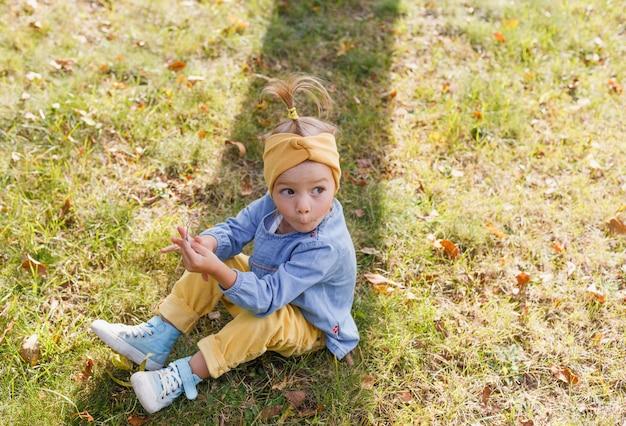 Mała dziewczynka w niebieskiej koszuli z zaskoczoną twarzą siedzi na trawie w parku