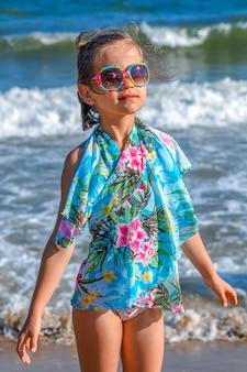 Mała dziewczynka w niebieskiej pelerynie plażowej i okularach przeciwsłonecznych na tle morskich fal
