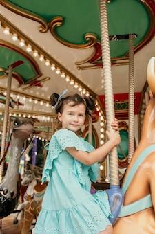 Mała dziewczynka w niebieskiej sukience jedzie na atrakcję w wesołym miasteczku