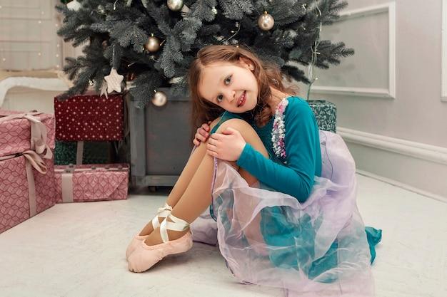 Mała dziewczynka w niebieskiej sukience na tle ozdób choinkowych