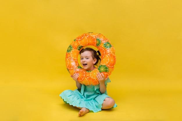 Mała dziewczynka w niebieskiej sukience siedzi z dmuchanym kółkiem na żółtym tle z kopią przestrzeni. wakacje
