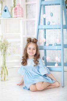 Mała dziewczynka w niebieskiej sukience zdobi dom na święta wielkanocne. niebieskie schody ozdobne z girlandą kolorowych pisanek. wielkanocne wnętrze. wiosenny wystrój domu. szczęśliwa rodzina przygotowuje się do wielkanocy.