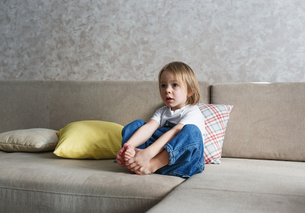 Mała dziewczynka w niebieskim, dżinsowym kombinezonie siedzi na kanapie, obejmując ją nogami