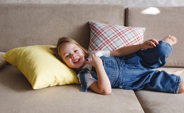 Mała dziewczynka w niebieskim kombinezonie dżinsowym leży w domu na sofie wśród kolorowych poduszek i uśmiecha się wesoło