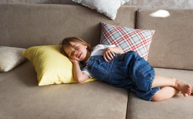 Mała dziewczynka w niebieskim kombinezonie dżinsowym śpi w domu na kanapie wśród kolorowych poduszek