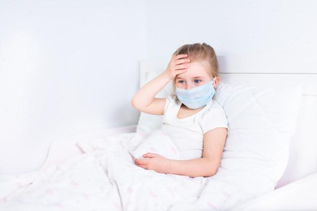 Mała dziewczynka w ochronnej medycznej masce zostaje w łóżku i dotyka jej głowę. ból głowy, migrena, koncepcja feaver.