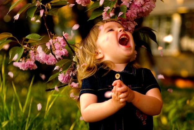 Mała dziewczynka w ogrodzie, pod drzewem sakura. wiosna