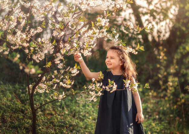 Mała dziewczynka w ogrodzie z kwitnącymi drzewami