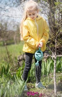 Mała dziewczynka w ogrodzie z zielonym garnkiem do podlewania