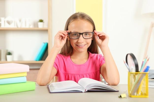 Mała dziewczynka w okularach czyta książkę w domu