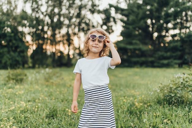 Mała dziewczynka w okularach i sukienkach, pozowanie na zewnątrz