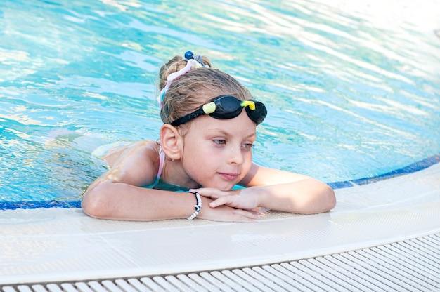 Mała dziewczynka w okularach pływackich pływa w basenie
